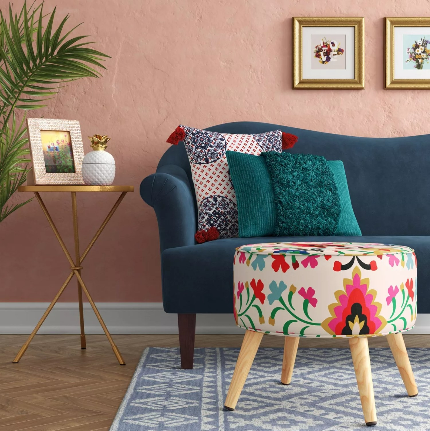 The ottoman with wooden legs and colorful flower pattern in a room with a couch and table