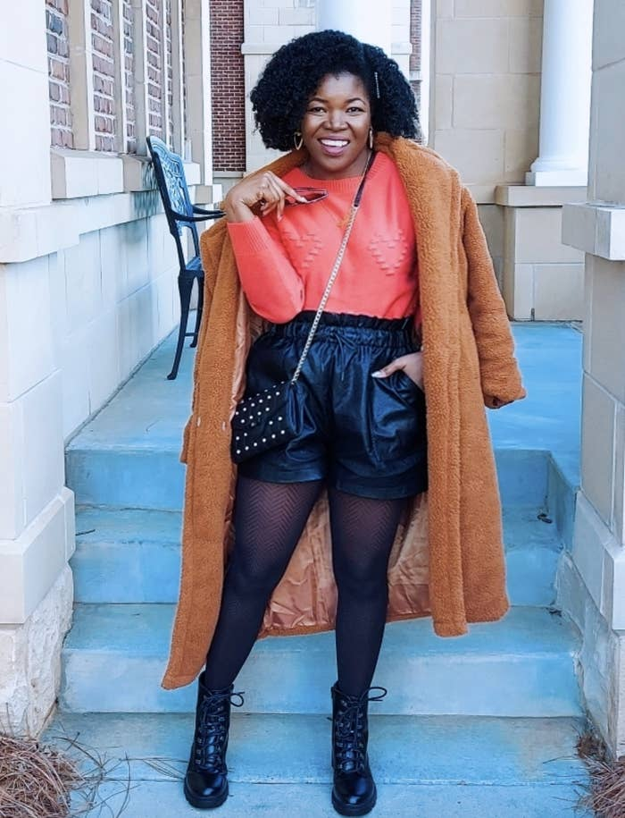 reviewer wearing the black faux leather shorts