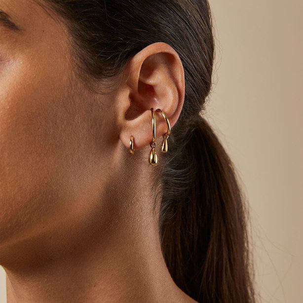 A person wearing a small hoop earring and two ear cuffs