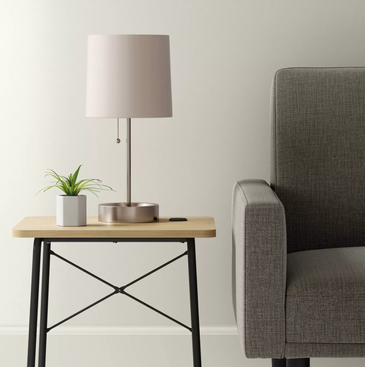 The lamp on a table next to a plant and the end of a couch