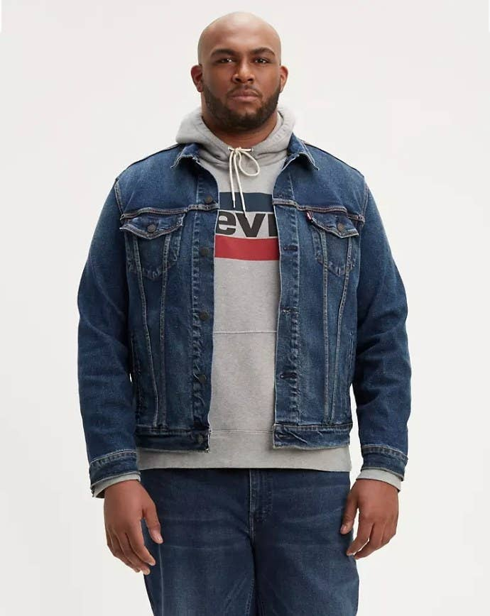 Model wearing dark wash trucker jacket with gray sweatshirt and matching jeans