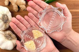 A pair of hands holding the garlic twist, which is made up of two transparent gear-shaped pieces with rows of teeth inside