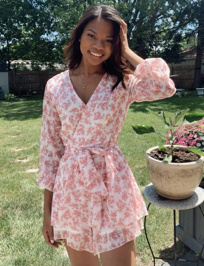 reviewer wearing the white and pink floral romper