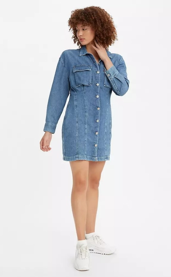 Model wearing long sleeve button up denim dress with white sneakers