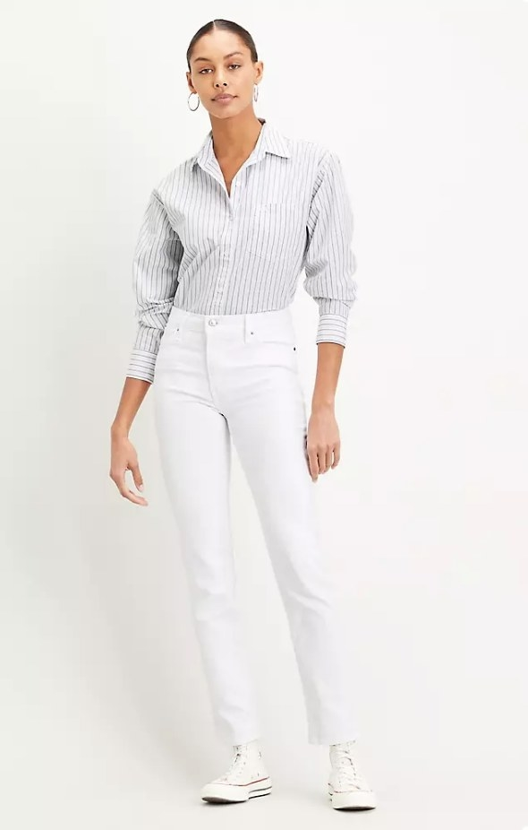 Model wearing white high rise jeans with pinstripe button down shirt