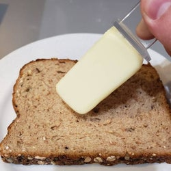 hand using it to butter a piece of bread