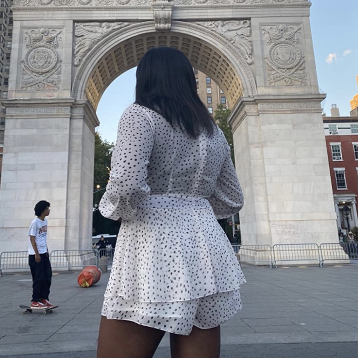 reviewer wearing the white and black dotted romper
