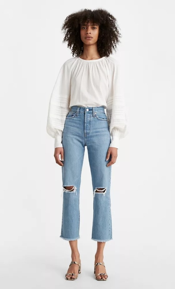 Model wearing light denim jeans with heels and white blouse