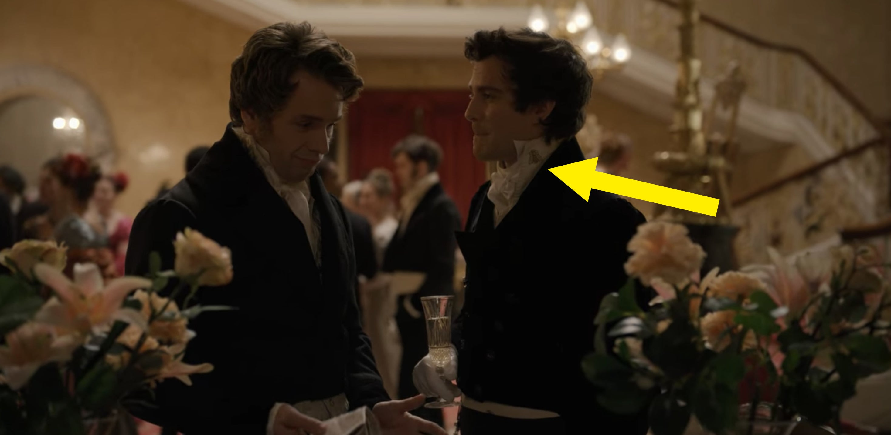 An arrow pointing towards Benedict's bee brooch on his collar