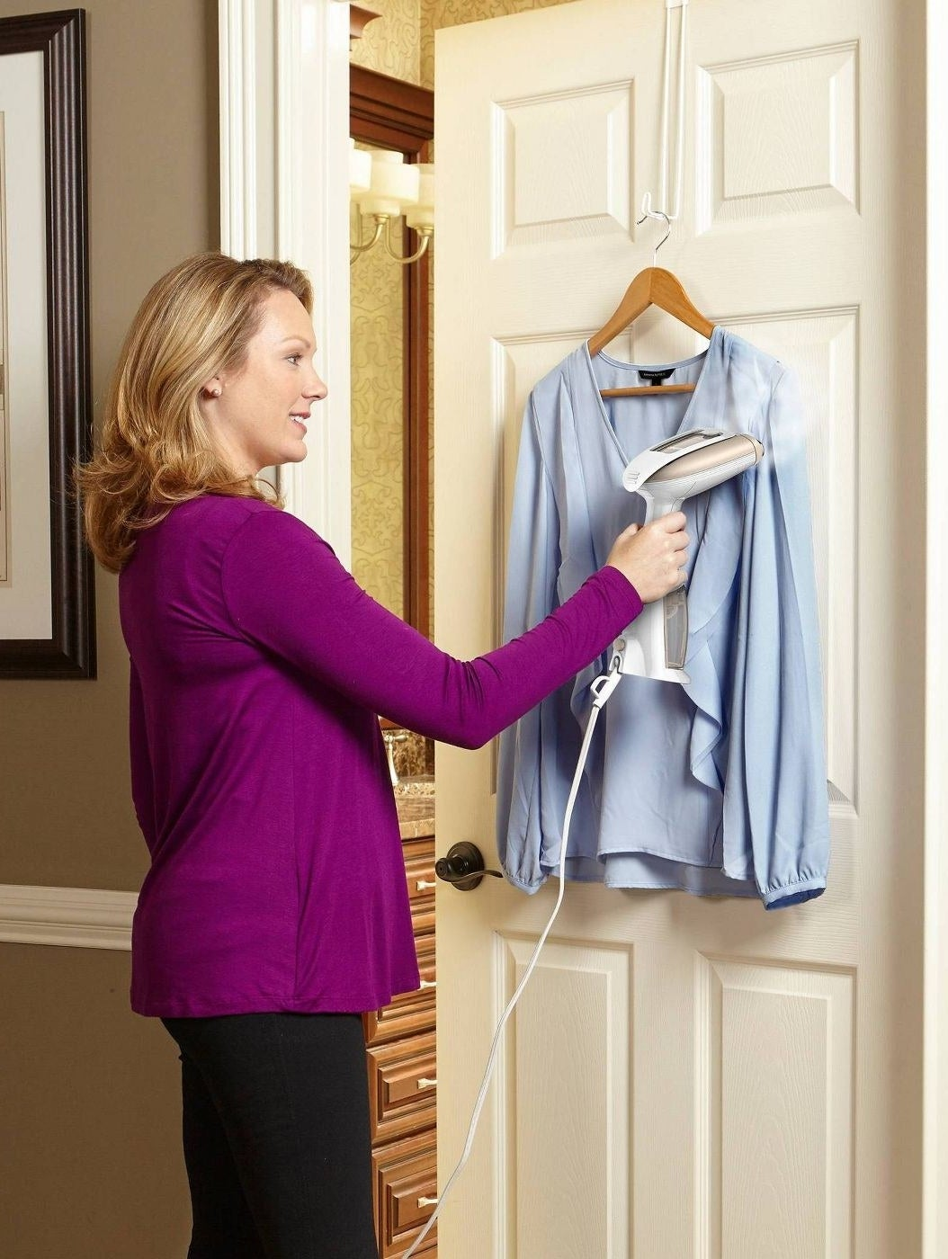 person using a white and gold garment steamer on a blue blouse