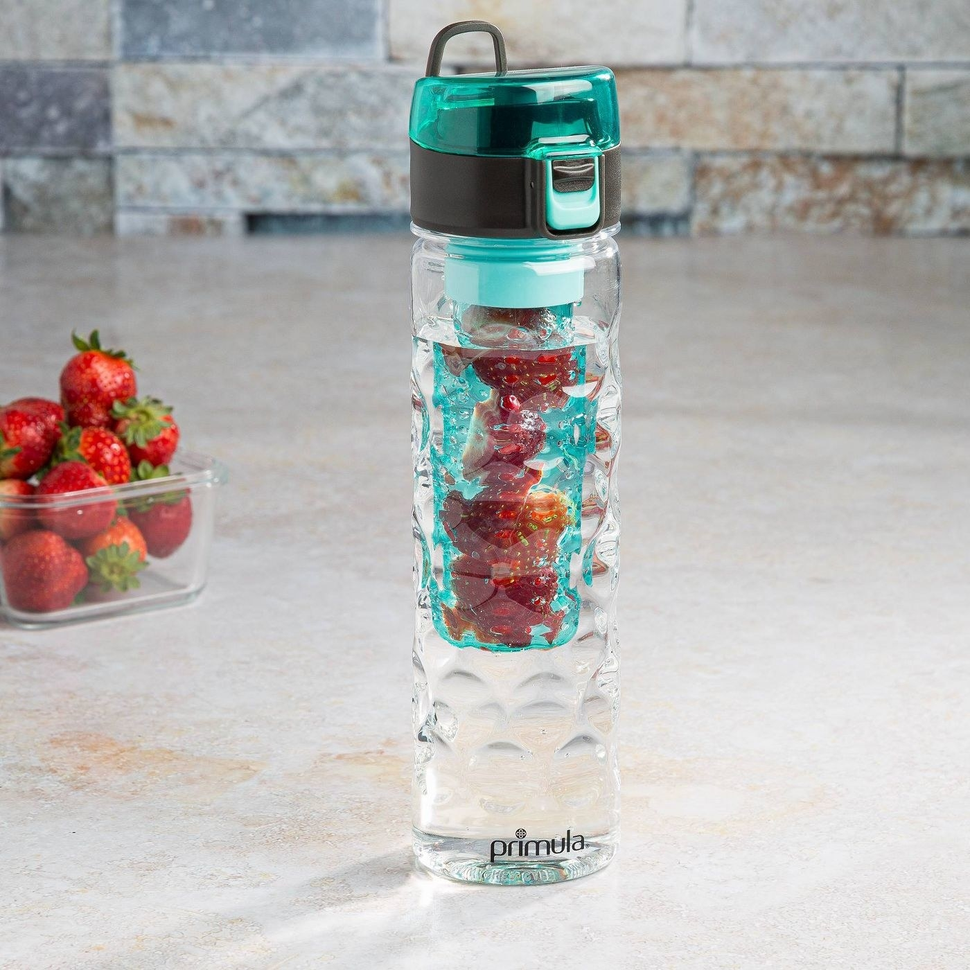 clear water bottle with a blue infuser that has fruit in it