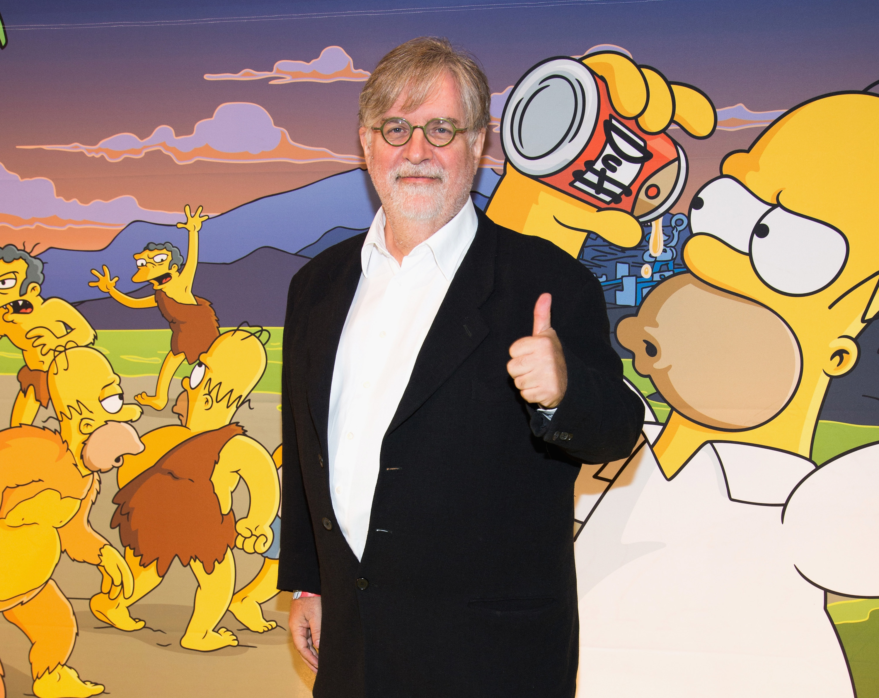 Simpsons creator Matt Groening gives a thumbs up in front of a Simpsons wall at an event in LA