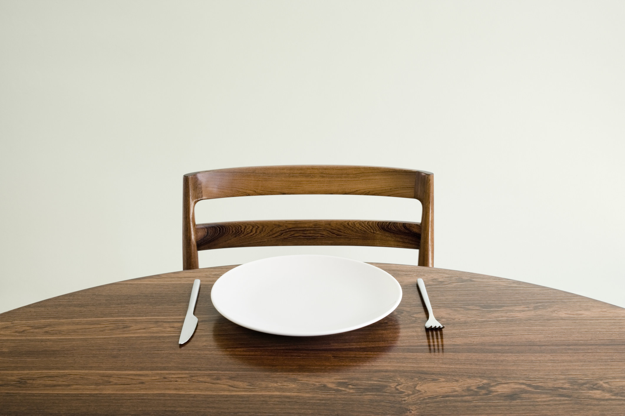 An empty seat at a table with an empty plate