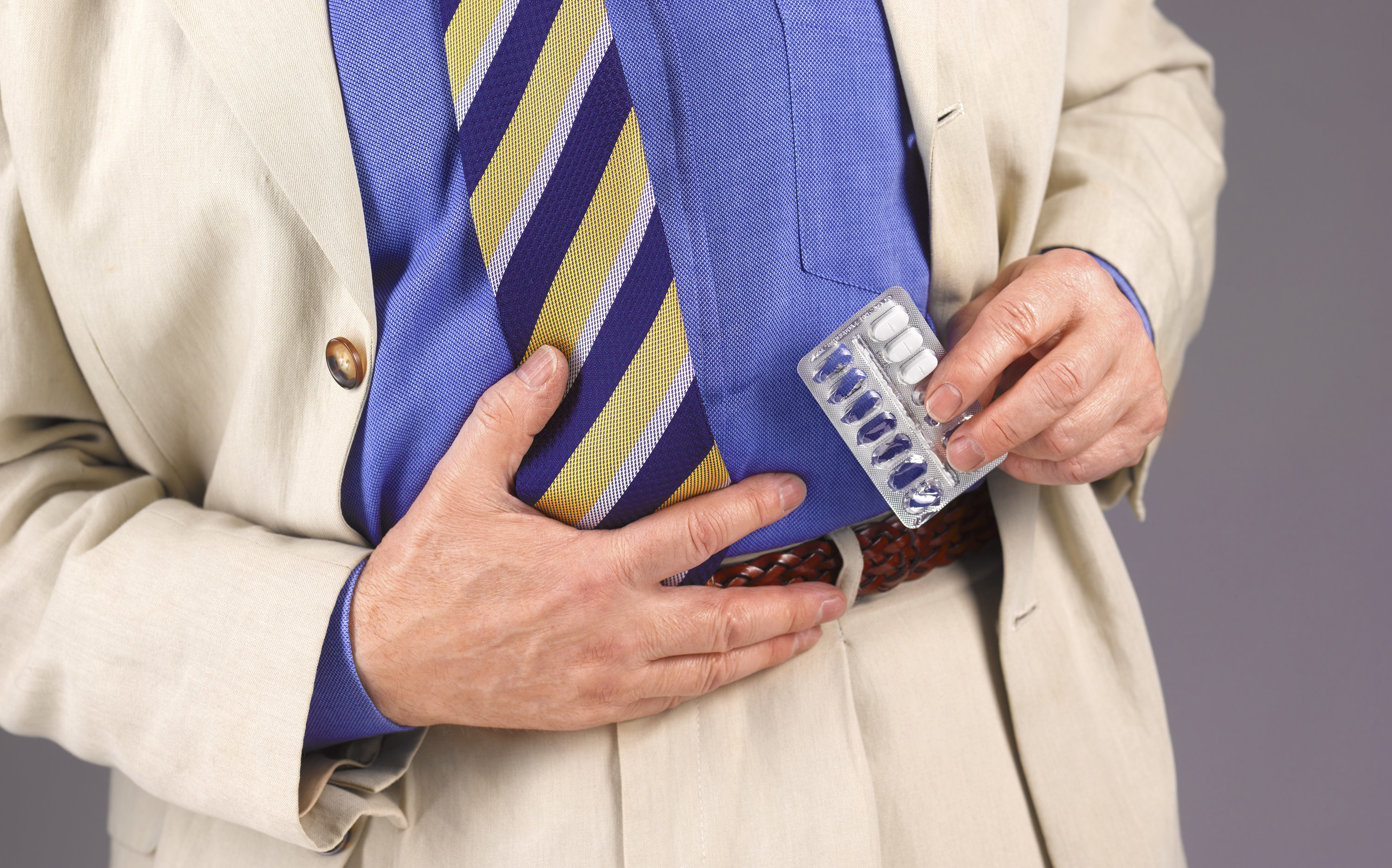 A man holds his stomach while also holding a packet of pills
