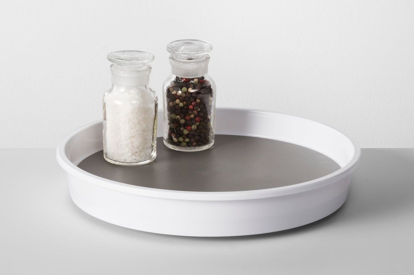 cabinet turntable with salt and pepper grinders on it