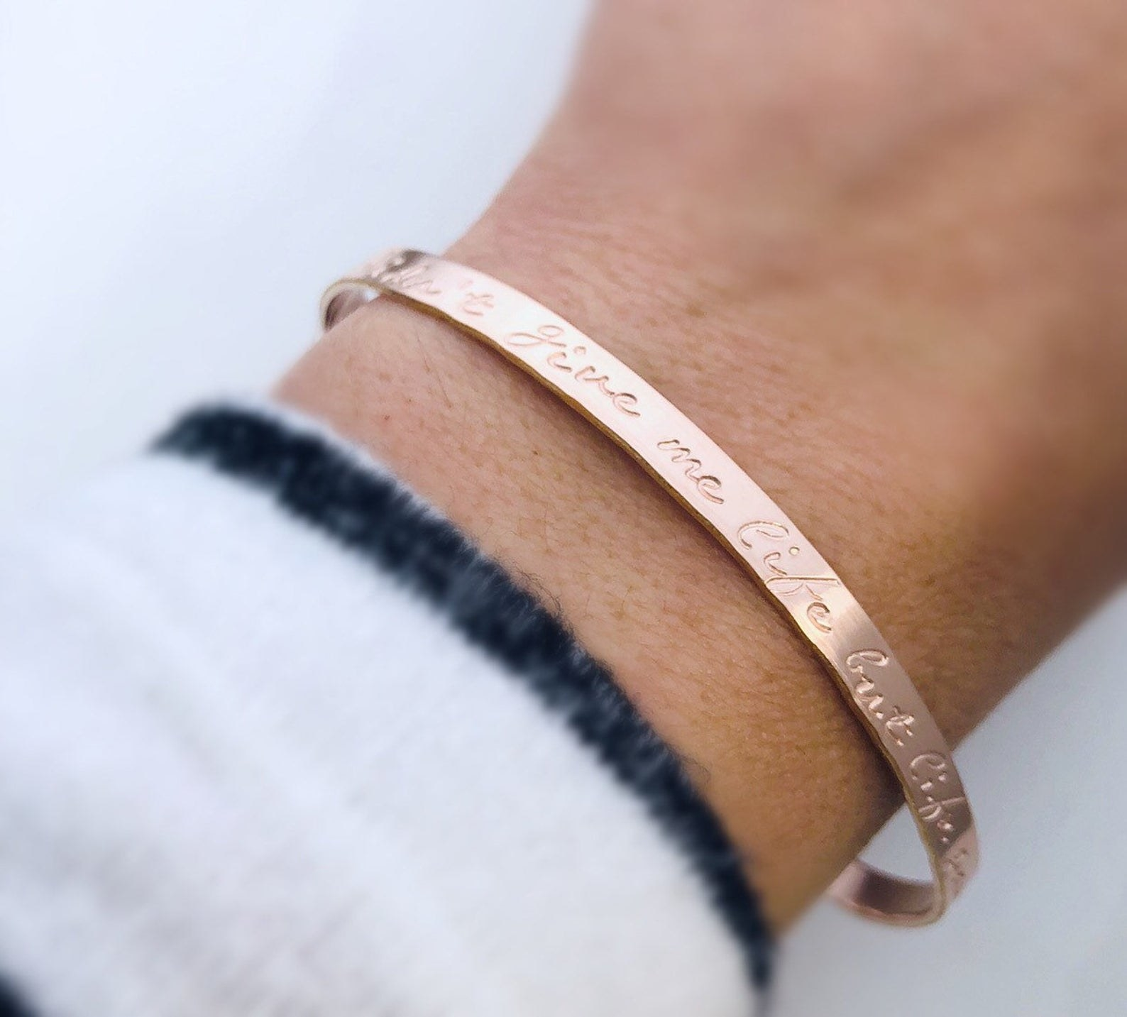 a model wearing an engraved cuff bracelet that says You may not have given me life, but life gave me you