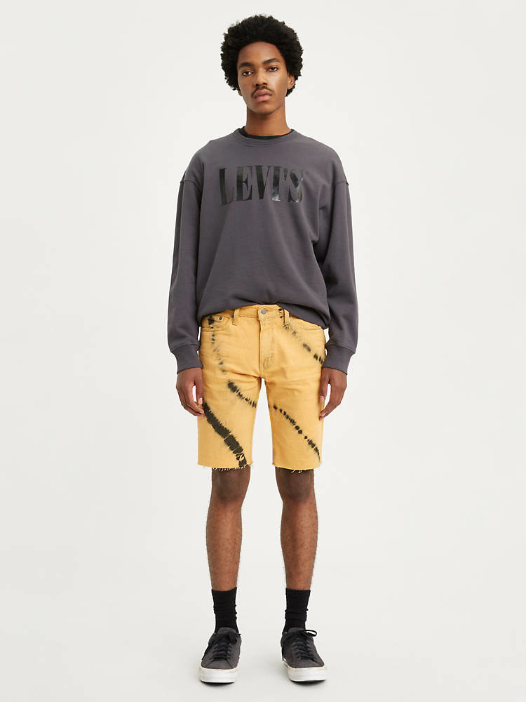 Model wearing yellow and black tie dye shorts with a gray crew neck