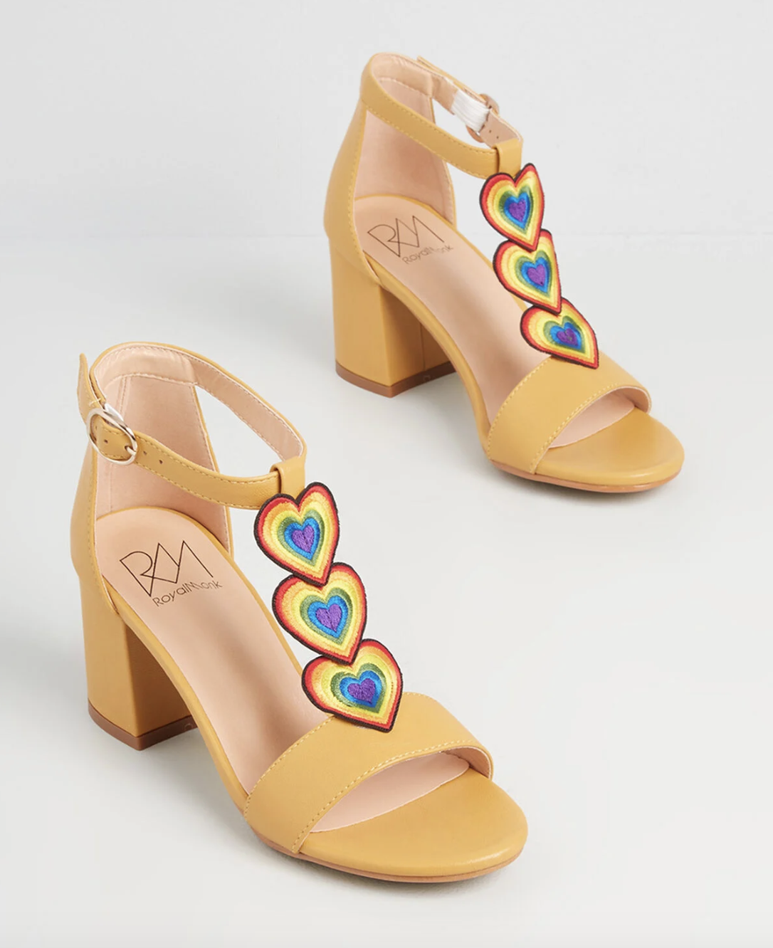 yellow heeled t-strap sandals with rainbow hearts on the straps