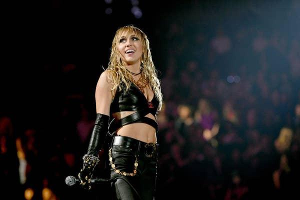Miley Cyrus mengenakan pakaian kulit di atas panggung