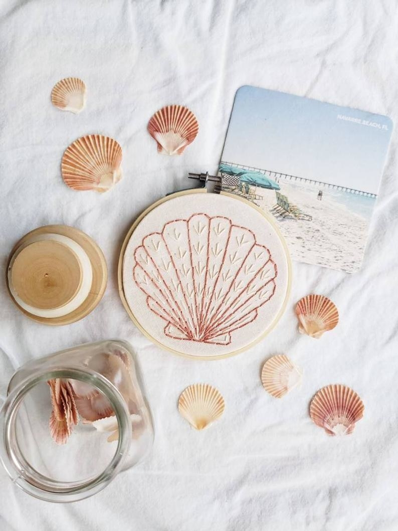 an embroidery hoop with the stitches of a seashell surrounded by real shells