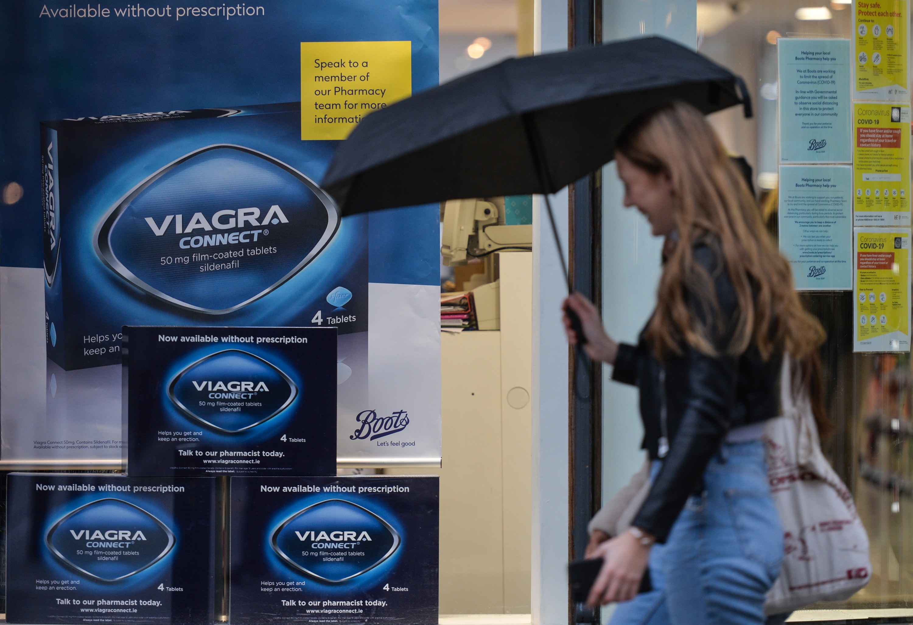 Woman walks past a Viagra connect add in a storefront
