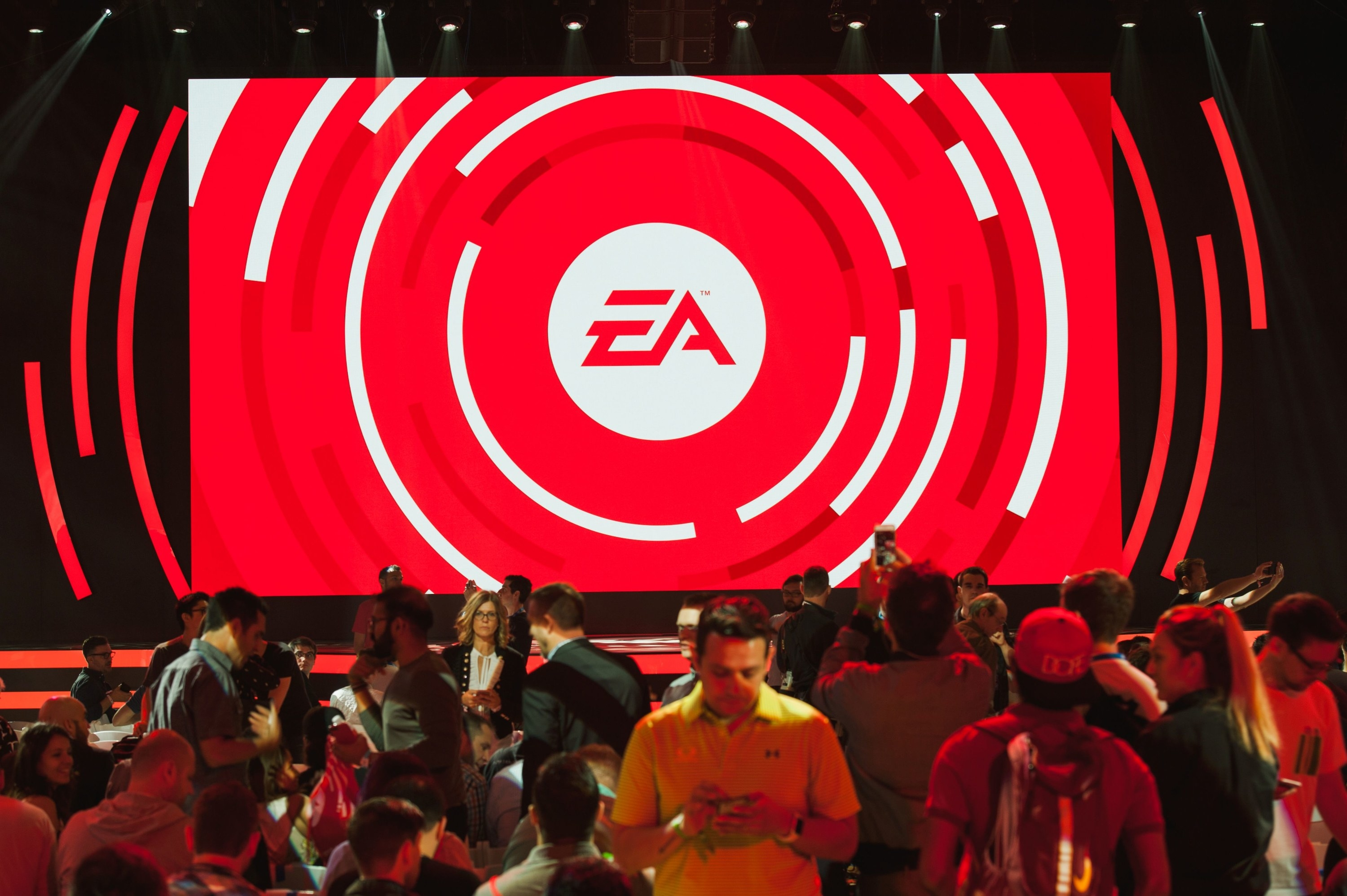 People attending an EA conference at the Hollywood Palladium with the EA logo on a large screen