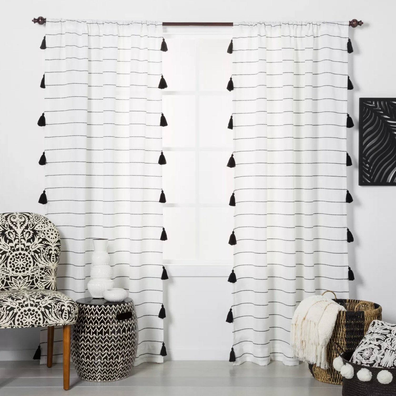 The black and white striped curtains with black tassels hanging on a black rod