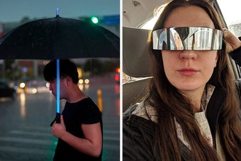 A person holding the umbrella, which has a shaft that glows like a lightsaber