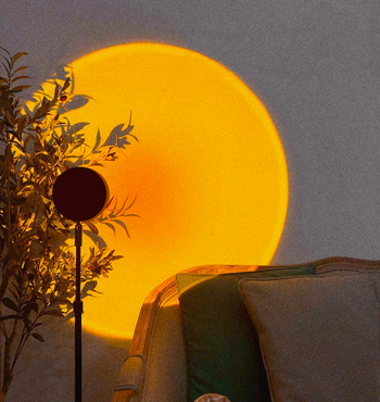 Upright lamp projecting round orange and yellow light onto wall