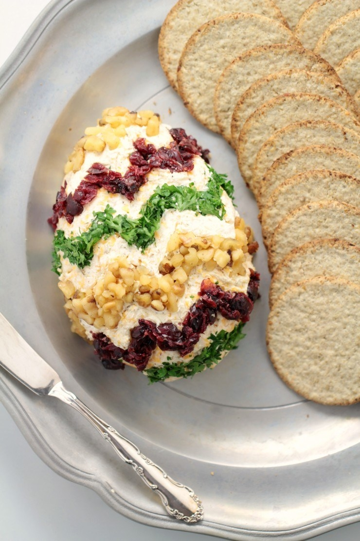An Easter egg cheese ball garnished with herbs, cranberries, and nuts.