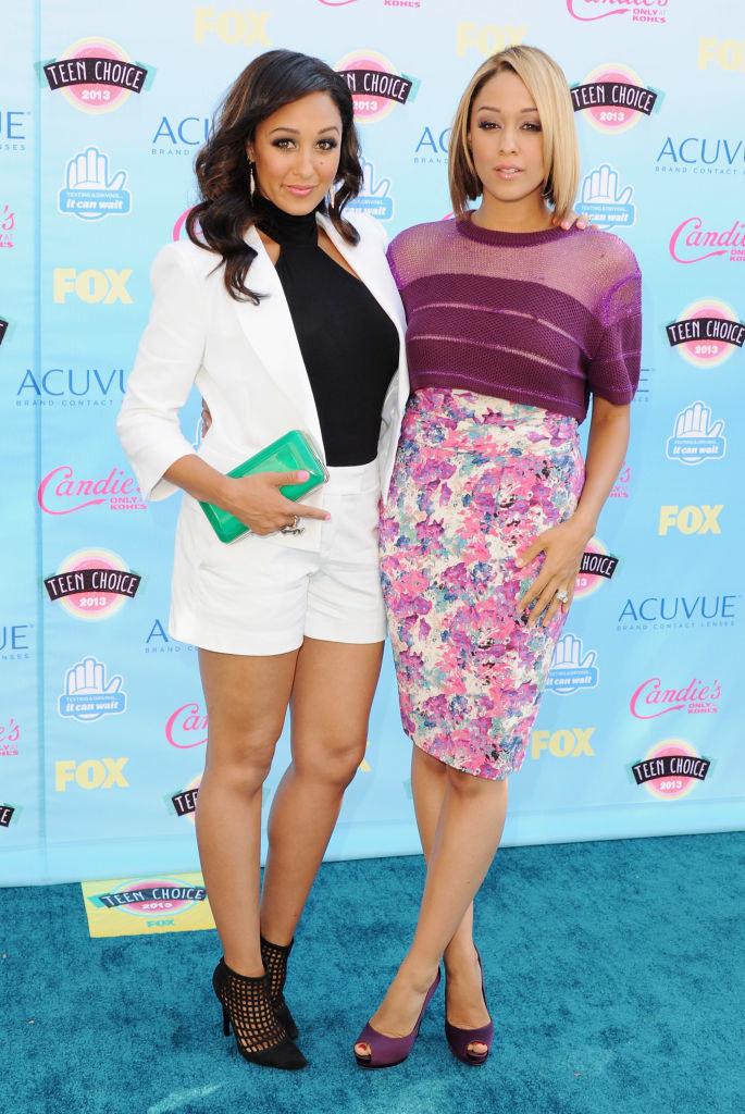 Tamera Mowry (L) and sister actress Tia Mowry on the 2013 Teen Choice Awards blue carpet
