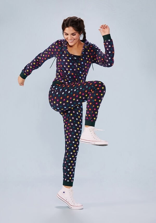 Model wearing rainbow-colored star print sweatsuit