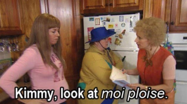 """Kath says """"look at moi ploise"""" to Kim while Sharon stands between them in their kitchen"""