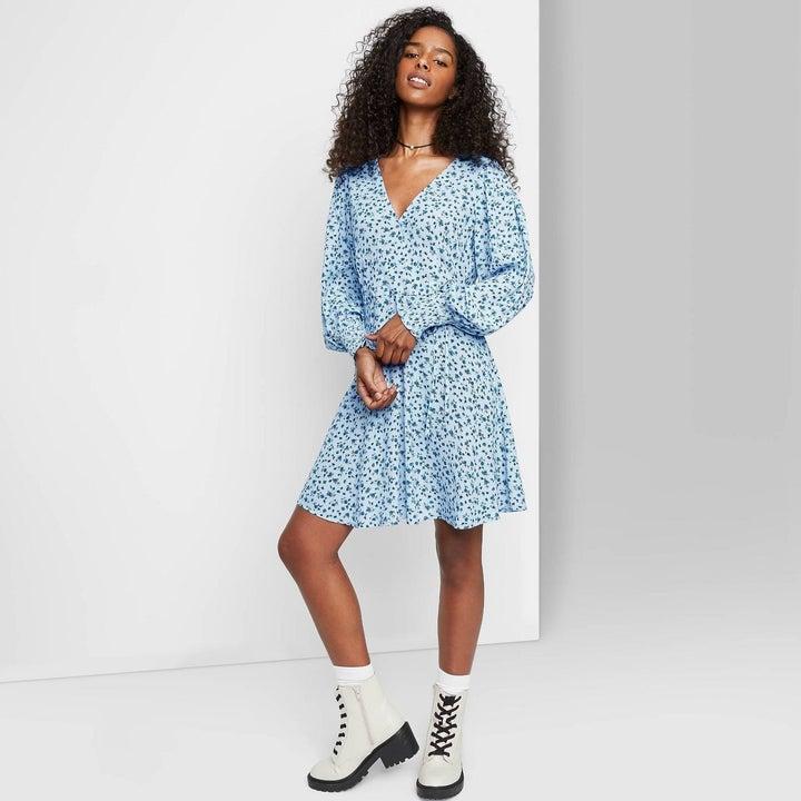 Model in blue floral long sleeve wrap dress
