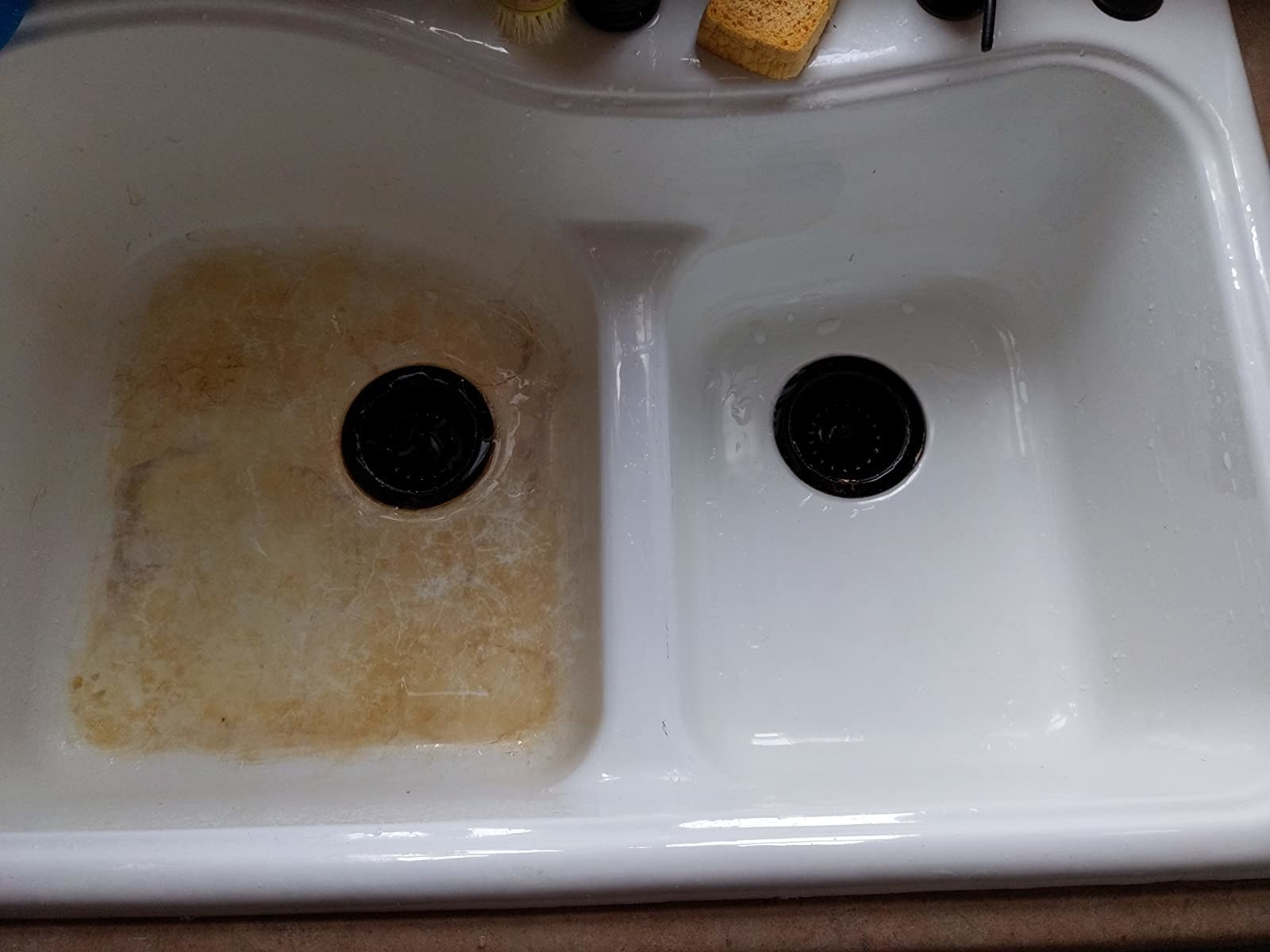 reviewer photo showing half of their sink has been cleaned with the sink cleaner, revealing the perfectly white, shiny surface beneath all the gunk and grime