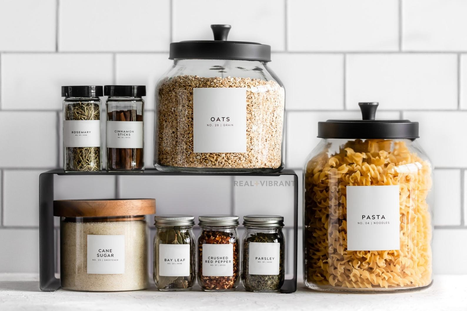 Glass jars of different sizes with square white labels saying what inside each one