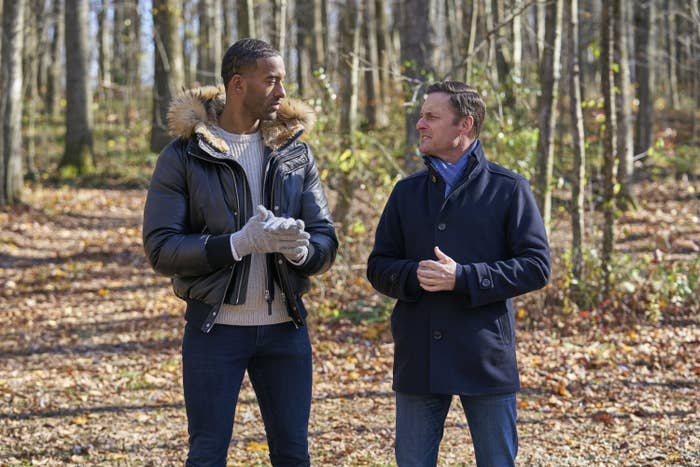 Matt James and Chris Harrison talking to each other in a wooded area