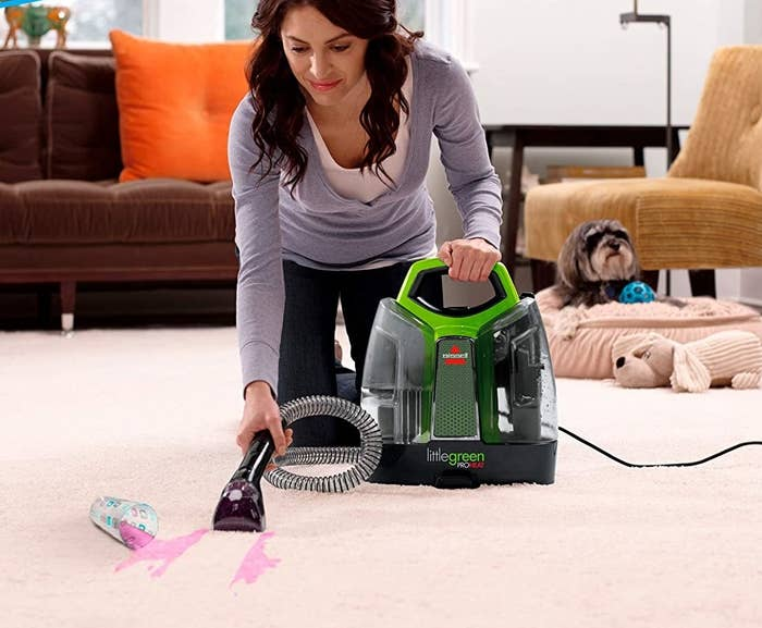 A person cleaning fruit punch off of a carpet with the deep cleaning machine