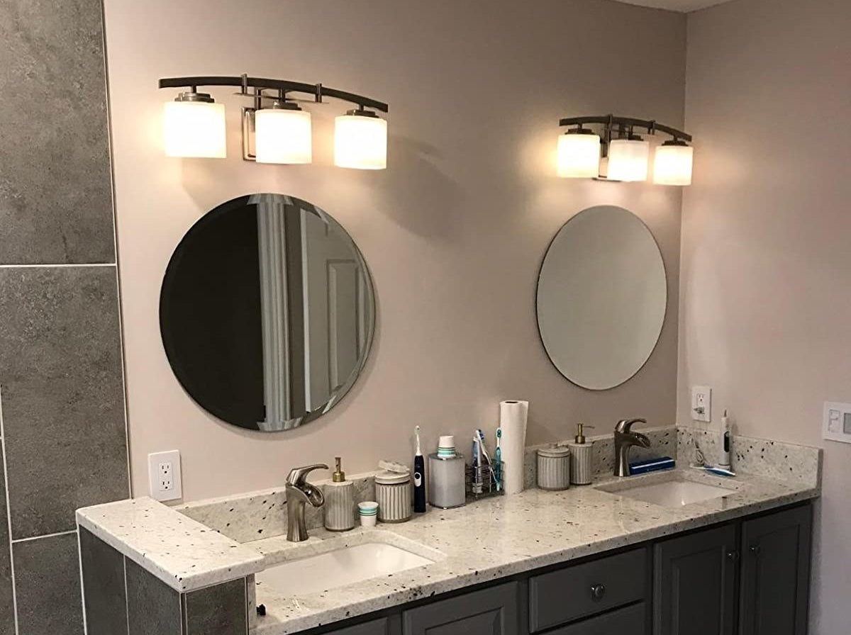 reviewer photo showing the round mirrors above the sinks in their bathroom