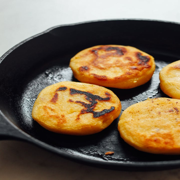 Arepas cooking in a cast iron skillet.