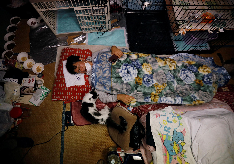 A man lies on a futon under a blanket with a cat