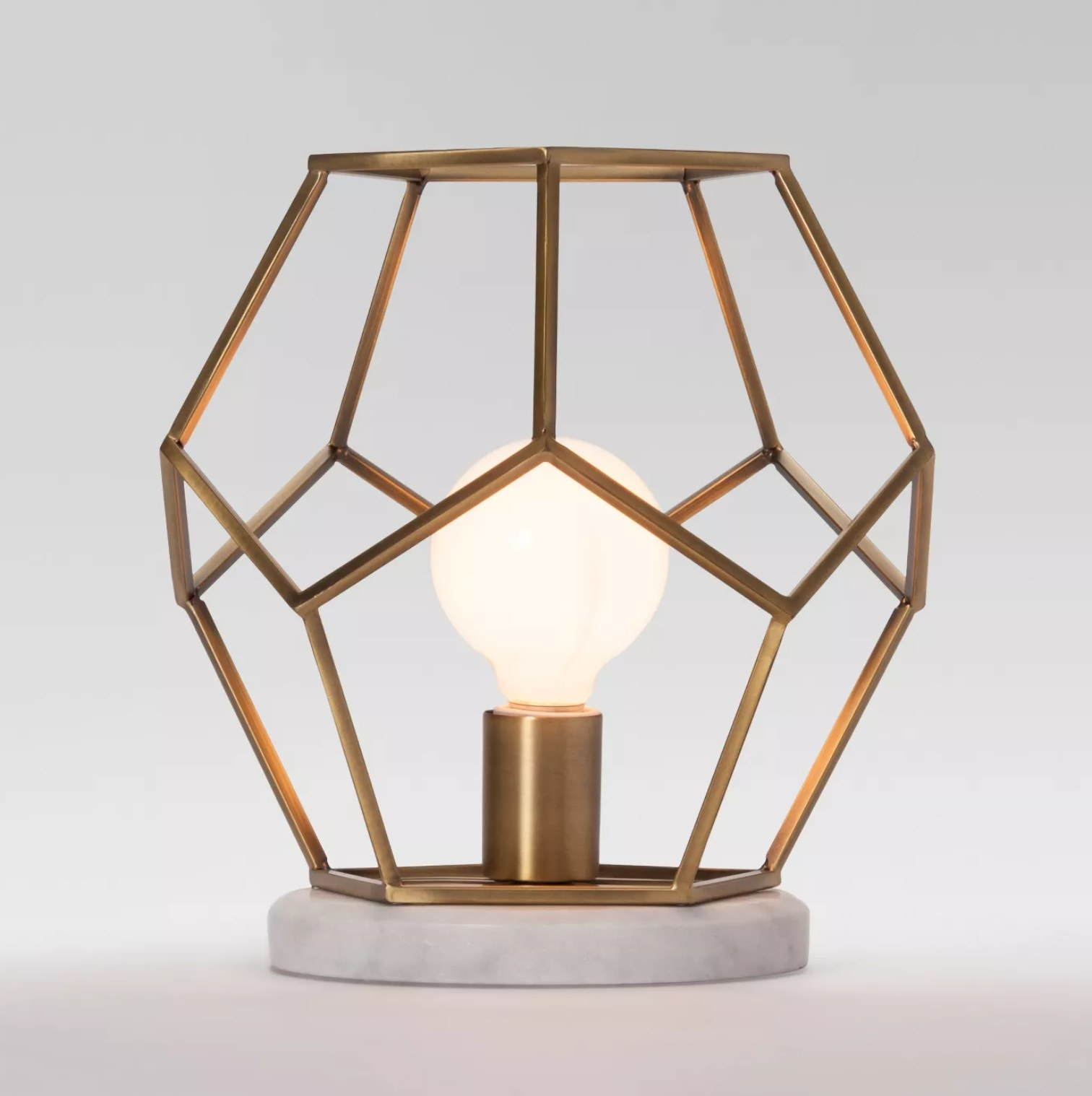 a hexagon shaped brass cage with an exposed bulb inside sitting on top of a marble base