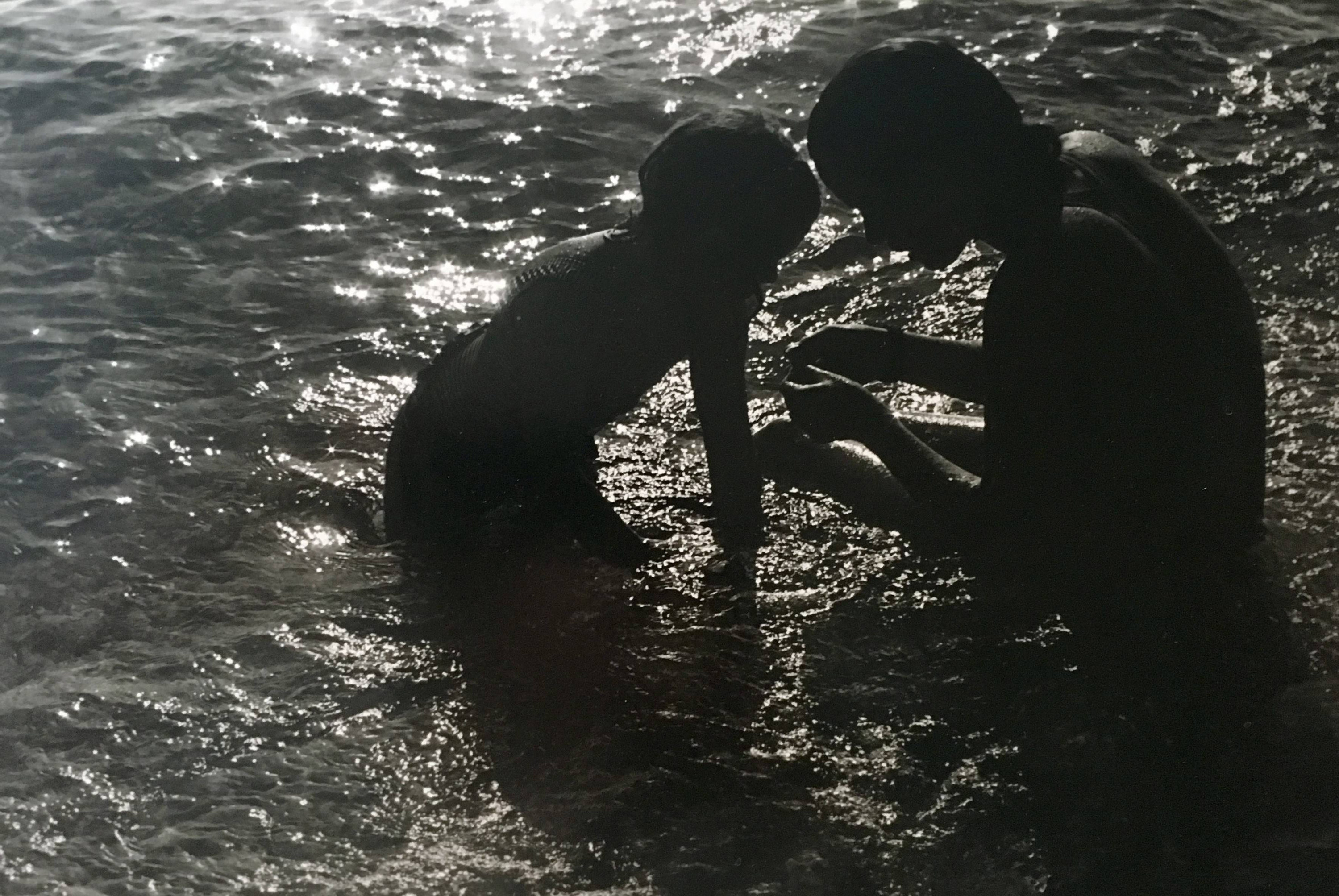 Two young girls at the waters edge examining something one of them is holding