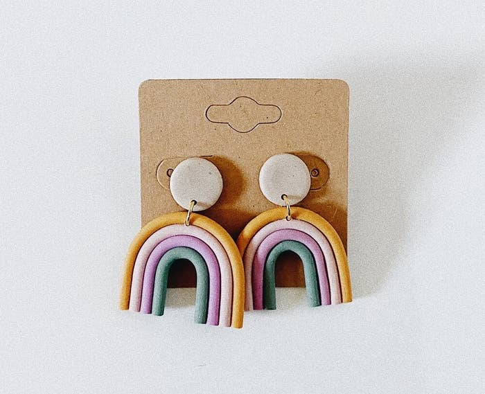 A pair of dangly clay earrings shaped like a rainbow