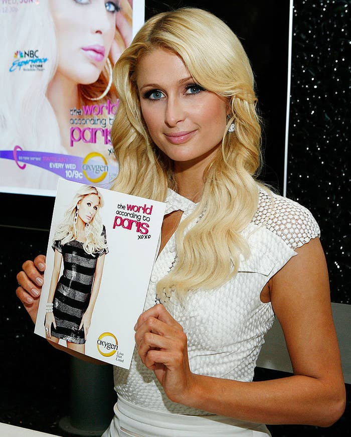 Paris posing with a photograph of herself  promoting the world according to paris xoxo