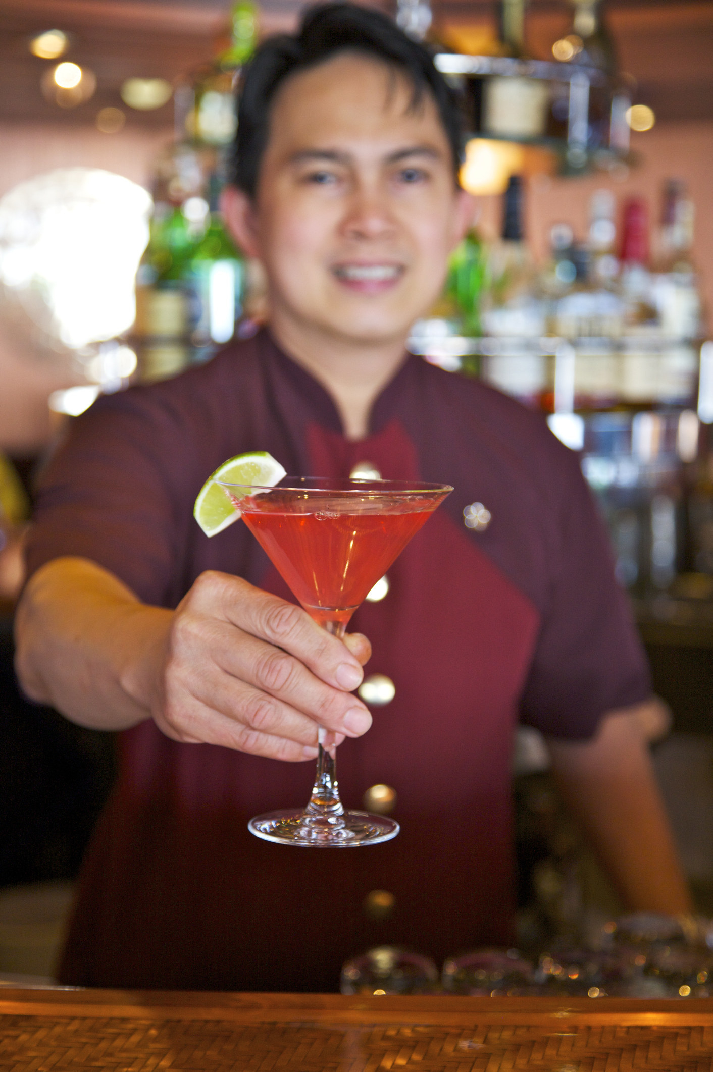 a bartender passing over a pink martini