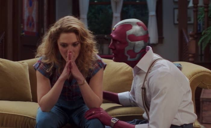 Wanda and Vision sitting on the couch and Wanda looking distraught