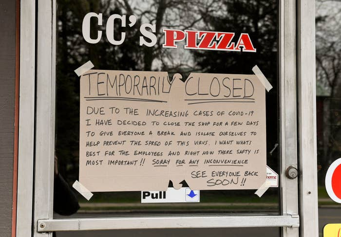 Pizza shop window with sign that says temporarily closed due to Covid-19