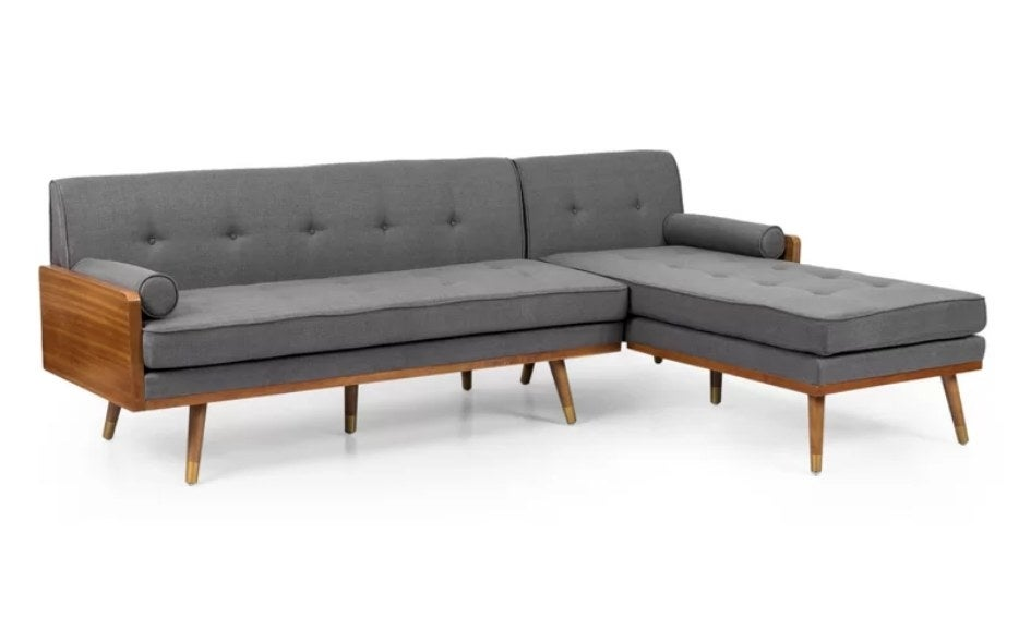 Gray chaise sofa with wooden legs and accents