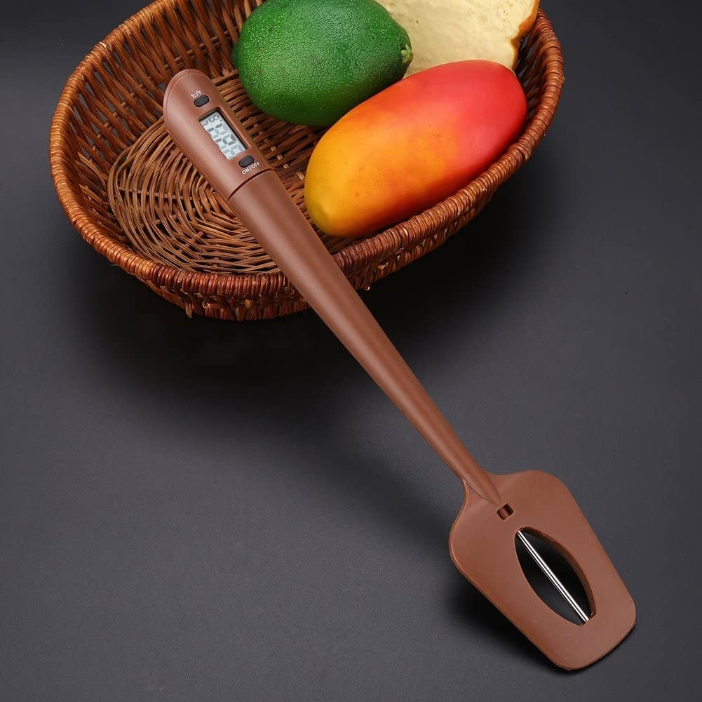 The spatula resting against a bowl of fruit